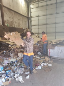 Workers separating trash and contaminated cardboard.